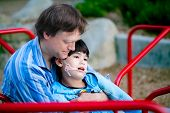 stock photo of merry-go-round  - Father playing with disabled son on merry go round at playground - JPG