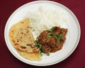 A kidney masala bhuna-type curry served with rice and paratha bread, garnished with coriander leaves