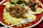 A plate of  beef rogan josh, served with yellow and white rice and a salad. Rogan josh is usually ma