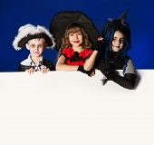 pic of warlock  - Happy children in halloween costumes posing over dark background - JPG