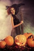 Beautiful red-haired witch casts a spell over pumpkins. Halloween.