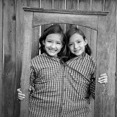 twin girls fancy dressed up pretending be siamese with dad shirt playing with grunge border frame