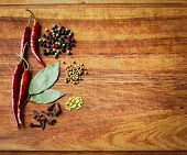 picture of bay leaf  - Dried red chili peppers and spices on rustic dark wood cutting board. Low key still life.
