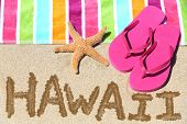 Hawaii beach travel concept. Hawaii written in sand with water next to beach towel and summer sandal