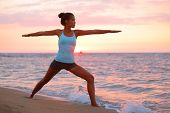 Yoga woman in zen meditating in warrior pose relaxing outside by beach at sunrise or sunset. Female