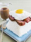 stock photo of loco  - Loco Moco a traditional common Hawaiian food made by stacking brisket on top of rice topped with a fried egg and covered in gravy - JPG