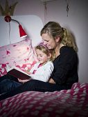 Mother and Daughter storytelling sitting on the bed