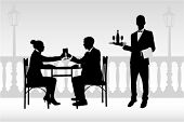 couple in restaurant holding glasses and waiter serving them