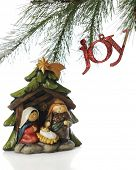 A simple nativity scene under the branches of a Christmas tree with a sparkly red