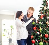 Young pregnant woman and happy father decorating Christmas tree