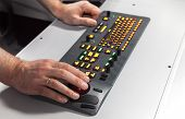 Hands On Illuminated Industrial Keyboard With Red Trackball. Selective Focus