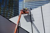 foto of cherry-picker  - View of new commercial buildings under construction with workmen in cherry picker - JPG