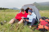 Couple on camping trip using a digital tablet outside their tent