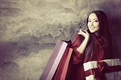 beautiful young woman holding colored shopping bags and gift box over grunge concrete wall, holiday
