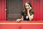 stock photo of caboose  - Portrait of happy young woman leaning on railing in red train caboose car - JPG