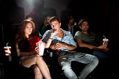 young people in a cinema attentively watching a movie, with popcorn and soda. An Asian woman feeding her boyfriend popcorn