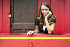 pic of caboose  - Portrait of happy young woman leaning on railing in red train caboose car - JPG