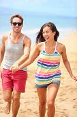 Beach vacation - happy fun romantic couple running holding hands. Two cool trendy hipster people playful on summer travel holidays. Interracial young couple, Asian woman, Caucasian man at ocean sea.