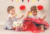 One-year-old twins behind decorated first birthday cake. Smash the cake party