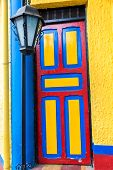 picture of medellin  - Brightly colored door in the colors of the Colombian flag in Medellin Colombia - JPG