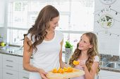 Happy mother looking at daughter as she picks a slice of sweet lime in the kitchen at home