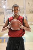 Portrait of African American basketball player with sweat on face holding ball