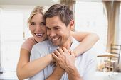 Close-up portrait of a happy young woman embracing man from behind at home