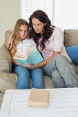 Little girl and mother reading novel together on sofa at home