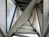 picture of girder  - Massive steel girder structure underneath a bridge that crosses a river - JPG