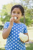 Portrait of a beautiful little girl eating cotton candy at the park