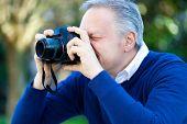 Senior man shooting photos in a park