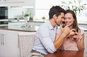 Loving young couple with wine glasses sitting in the kitchen at home