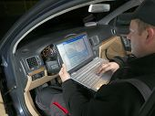 Auto mechanic checking vehicle identification number of the car using laptop hooked up to the car onboard computer