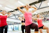 fitness, sport, training, gym and lifestyle concept - group of smiling female with trainer exercising in the gym