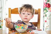 Boy making a face while eating breakfast cereal