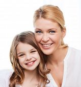 family, child and home concept - smiling mother and little girl at home