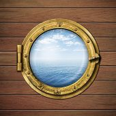 boat window or porthole on wood wall with sea or ocean horizon behind it