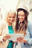holidays and tourism concept - beautiful girls toursits looking into tablet pc in the city