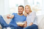 food, love, family and happiness concept - smiling couple with popcorn watching movie at home