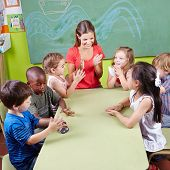 Group of children clapping hands in kindergarten in musical education class