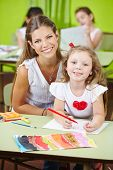 Happy child care worker helping girl painting in a kindergarten
