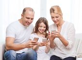 family, child, technology and home concept - smiling parents and little girl with smartphones at home