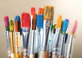 image of bristle brush  - several used paintbrushes with colorful oil paints
