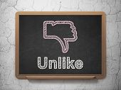 Social network concept: Thumb Down and Unlike on chalkboard background