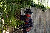 Cowboy Ambushing In Bandana Behind Eucalyptus