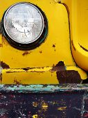 Closeup detail of old bumper and headlight on truck car scraped paint chips