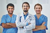 Portrait of three successful clinicians in uniform looking at camera