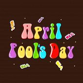 April Fool's Day concept with colorful glossy text on brown background.