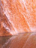Red Orange Stone Reflecting in Pool of Rain Water