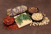 Frankincense, myrrh, sandalwood, incense cones , cedar leaf and smudge stick over lokta paper backgr